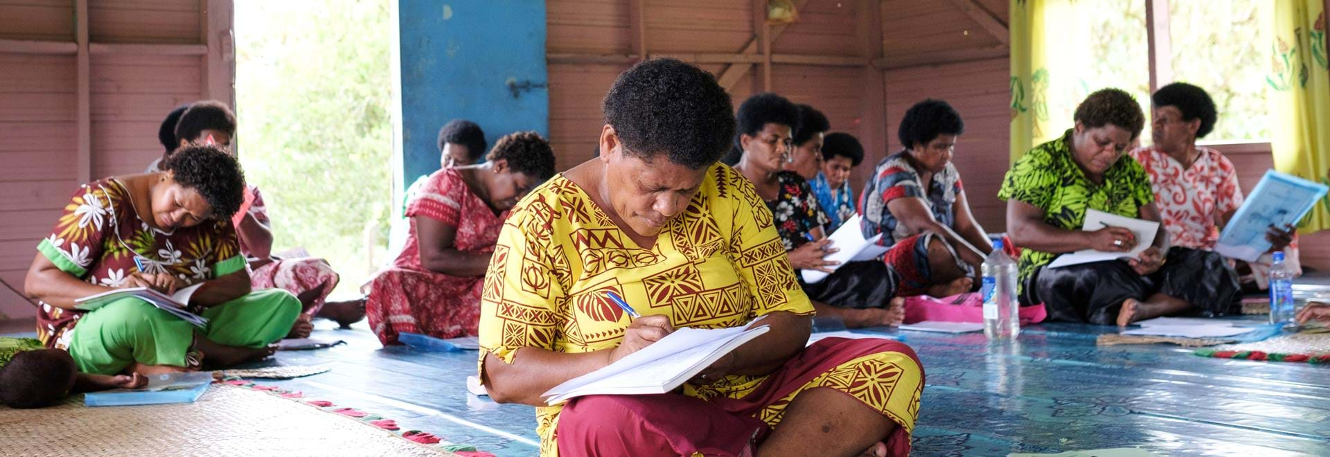 A group of Fijian women sitting in a room writing in notebooks