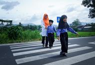 Indonesian schoolchildren and their mother crossing a road built through PRIM