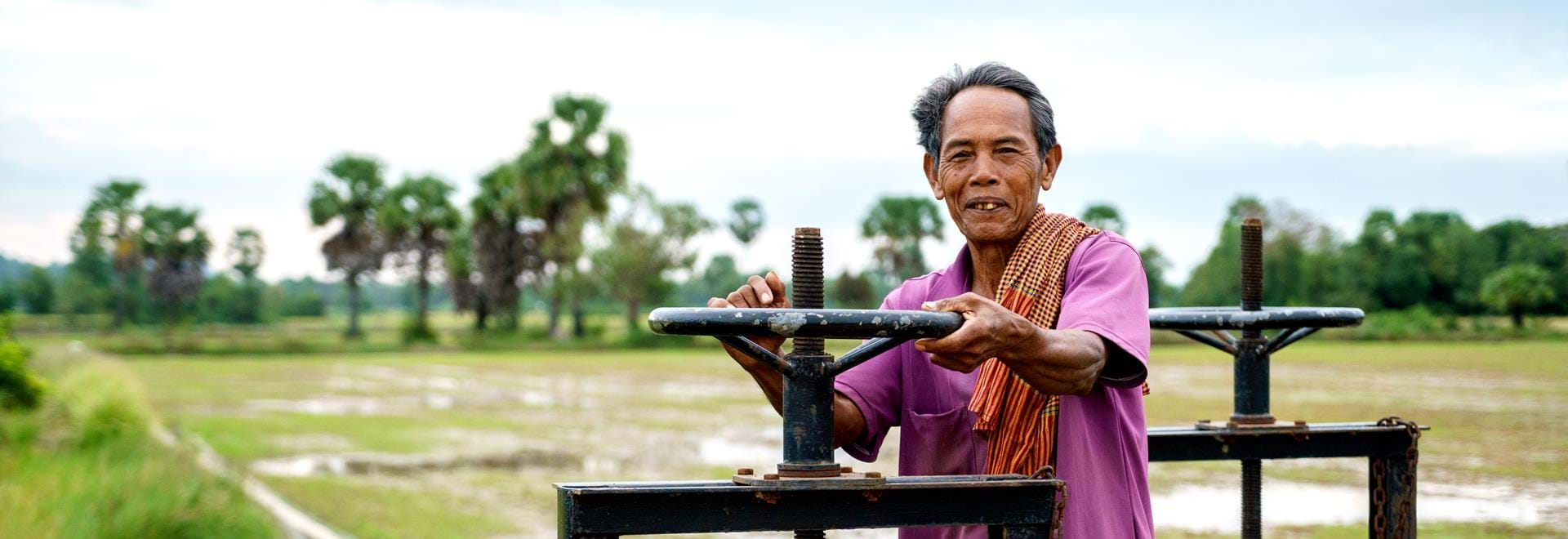 Cambodian man using water pump in field